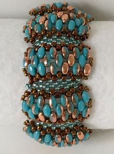 This stunning Turquoise and Gold Bracelet and Earrings set is bead woven, using Czech SuperDuo glass beads in Apollo Gold and Turquoise/Gold. It is done in a wave design, adding in Japanese Bronze seed beads and a Metallic Copper Luster. The bracelet clasp is in Antique Bronze. They