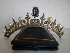 An early combe featuring floral gilt motifs with button pearls and a central amethyst surrounded by seed pearls