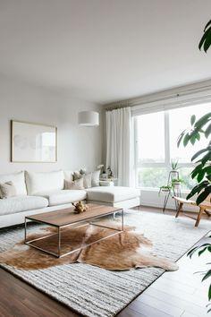 sala de estar en estilo escandinavo con paredes y muebles en blanco y alfombra vaca, salones modernos de diseño