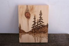 This beautiful lakeside scene has been burnt into a piece of salvaged pine wood with a process known as Pyrography (commonly referred to as wood burning) The knot in the wood creates the sun in the sky. The reflection ripples along the waters edge. A hook has been added to the back for easy hanging. Measures 10 inches tall by 7 3/4 inches wide and is signed and dated on the back. A wonderful and rustic addition to your home, cottage or summer hideaway