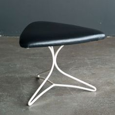TITLE: Triangular stool designed in the 1950's by Vladimir Kagan.  PRICE:$911 Purchase >  CREATOR: Vladimir Kagan (Designer)  COUNTRY: United States  CREATION DATE: circa 1950  MATERIALS: Enameled steel, black leather  CONDITION: Excellent  LENGTH: 19.69 in. (50 cm)  DEPTH: 19.69 in. (50 cm)  HEIGHT: 15.75 in. (40 cm)  DEALER LOCATION: DRONTEN, EUROPE  NUMBER OF ITEMS: 1  REFERENCE NUMBER: LU9314782504