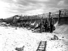 """These German prisoners relax in front of the sea wall of Bernières sur Mer. Behind them is post Wn (Wiederstand Nest) 28 which formed part of the """"Atlantic Wall"""" defences in that area. This post was garrisoned but Company 5, II Battalion, Grenadier Regiment 736 of Infantry Division 716."""