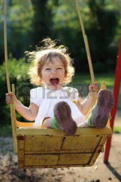 Niño riendo en el columpio en el parque de verano