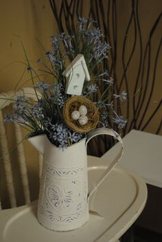 Flower arrangement in a old watering can with a bird house and nest.