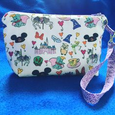 Our Magic Kingdom wristlet, which is available in the four featured fabrics, is perfect for a day in the parks or a night out where you just want to show off a little bit of your Disney love.  The wristlet features an interior pocket, is 5 inches by 8 inches and the strap is 13 inches long.