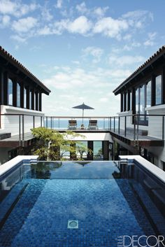 Constructed into the side of cliffs that face the Atlantic Ocean, Kasia Krynska's home in Cape Town, South Africa, designed by TMA Architects, features a central courtyard with an elevated pool. A bridge connects the house's study, left, and master bedroom.