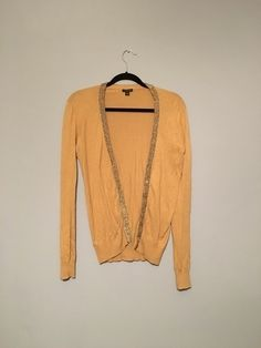 This is a cardigan from Ann Taylor. It is an extra small and it is so cute. It is tan but the trim is a sparkle gold. Plea...