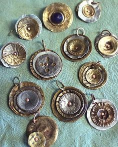 Buttons! Smooshed metal buttons Cut off any shanks with Tim Holtz Tonic scissors and then you can crush them in the old pull lever Sizzix machine or a QuicKutz handle or on concrete with standard hammer. Drill hole and add jumpring. Not sure what any of