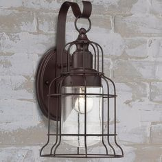 Large Industrial Oceanside Wall Sconce An adaptation to the classic nautical caged lights, this outdoor wall light boasts an enclosed clear seeded glass shade behind a bell shaped cage. The combination results in a vintage inspired updated nautical outdoor light with an industrial flare. Use outdoors or indoors, perfect for farmhouse style bathrooms and hallways