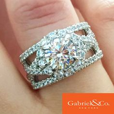This 18k White Gold Diamond Halo Engagement Ring by Gabriel & Co. is a big and bold statement! This gorgeous ring has two lovely criss cross bands along with two straight bands filled with many other diamonds. What a unique and stunning engagement ring!