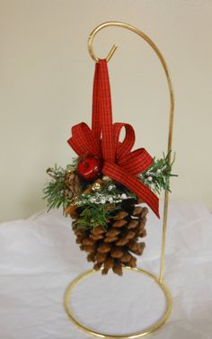 Christmas is right around the corner! These beautiful pine cones were handpicked in various states. Decorated with greenery, apples, berries/beads, cinnamon sticks, and mini pine cones, and a red ribbon. Measures 6 to 7.5 inches long Sold in a set of 2. These ornaments would be a