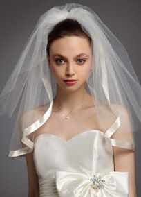 A classic piece with an updated edge, this satin veil is the perfect finishing touch on your special day.  Satin veil comes with attached blusher.  Edge is accented with ribbon trim.  Available in ivory and white.  Made in USA.