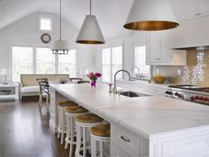white kitchen with marble and vaulted ceiling