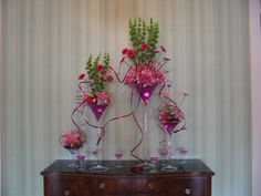 Entry table composite - large martini glasses with flowers and hot pink pearls accented with coiled wire.