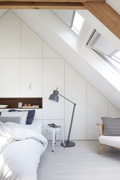 Having 2 skylights adds so much light to this converted attic! Beautiful white built-in storage has created a seamless bedroom.