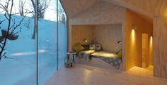 Rifugio in Norvegia. Precede la zona notte questa ampia stanza panoramica, dalle vetrate a tutt'altezza. In un angolo, i progettisti hanno ideato un vano letto, pensato per la lettura e il riposo diurno.