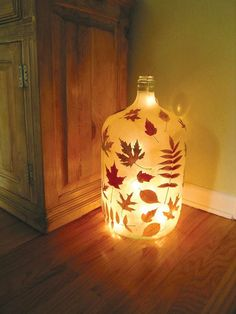DIY Luminous Bottle - A large empty glass bottle rescued from a restaurant's dumpster.U se Mod-Podge (or similar) to cover with pressed autumn leaves,  a layer or two of tissue paper.  Then fill with a string of lights to create this luminous vessel.