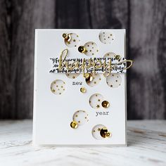 gold glittery stars bring new years wishes this white card base has been punched randomly with circles and popped up on a layer of paper with gold foil