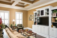 Great room with custom built-in shelves and entertainment center and coffered ceiling treatment. Designed and built by Ramage Company.