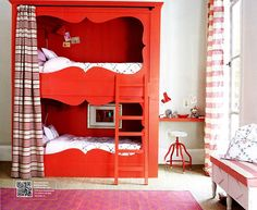 via British Home & Gardens custom curtained bunk beds painted red.  Pink and orange Madeline Weinrib rug. Kids bedroom