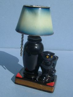 I am selling this terrific old late 1940s retro table lighter.  The unusual cigarette lighter is in the form of a ceramic lamp and black cat standing on the top of a book.  The shade s the lighter and it screws onto the lamp.  It was manufactured by Evanus and measures 5 3/8 inches high and 3 1/4 inches wide.  When you pull down on the chain to the side of the lamp, the lighter pops up.  It would need flint and petrol.