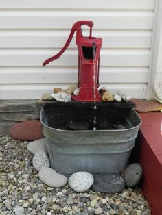 Old water well pump and a tub makes a unique water feature.