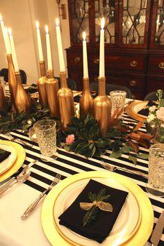 servilletas negras y centro de mesa de botellas de color oro