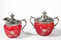 "OPEN-HEART ARCHES CREAM AND SUGAR SET, pigeon blood/ruby red with satin finish and polychrome-enamel floral decoration, each with quadruple-plate mount. Possibly Consolidated Lamp & Glass Co. or Pittsburgh Lamp, Brass, & Glass Co. Late 19th/early 20th century. 5"" and 5 3/8"" HOA."