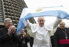 Pope Francis holds up Argentina's flag outside cathedral during World Youth Day visit to Brazil  Pope Francis holds up Argentina's flag as he greets a crowd of World Youth Day pilgrims outside the cathedral in Rio de Janeiro July 25. (CNS photo/Paul Haring)