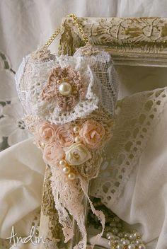 Srdíčko ve stylu Shabby chic Závěsná dekorace v barvách smetanové, starorůžové a v tonech bílé kávy. Zdobení růčně tvořenými růžičkami, , krajkami a perličkami. Průměr 10 cm, bižuterní řetízek na zeavěšení ve zlaté barvě