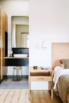 Classic wood headboard with a modern matching wood nightstand and white wall lamp