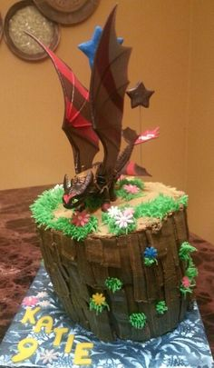 How To Train Your Dragon Cake - Kit Kats on the side with grass, flowers, water and rocks on top.