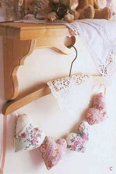 Love this idea to shabby chic a wooden clothes hanger with a lacy doily and a string of little padded hearts.....
