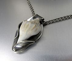 I made this pendant with a tiny shell I found on vacation.  The setting is fine silver.  The shell is wired on in the back.