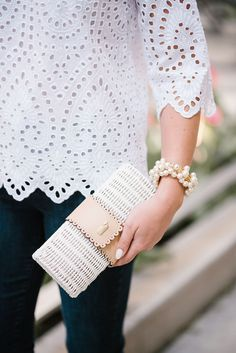Chicago blogger Jessica Sturdy of Bows & Sequins holding a Vineyard Vines white wicker rattan clutch and wearing a Sweet & Spark pearl bracelet.