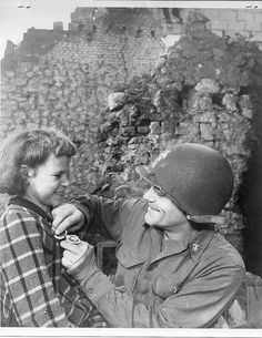 Chief Machinist Trammell presents his own Purple Heart (which he earned when he suffered wounds from a German 88 millimeter shell near Geilenkirchen) to Rosa De Greief whose life he saved when he rescued her from her bomb wrecked home in which her mother and sister perished.