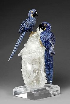 <i></i><i>By Peter Mueller<br />Brazil</i><br />Each carved of bright blue sodalite from Brazil, with inset rubellite cabochon eyes and yellow agate checks. The gold vermeil feet resting on a Brazilian rock crystal quartz cluster with transparent crystals. Raised on a acrylic base, <i>height 20in</i><br /><i></i>