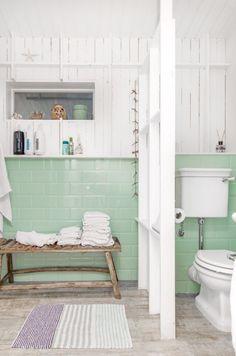 miętowy kolor ceramicznych płytek na ścianie w białej łazience z ażurową ścianką