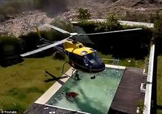 Incredible moment firefighting helicopter runs out of water so hovers above nearby swimming pool and refills swinging bucket