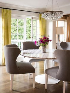 Molly Sims's dining room | white marble tulip table with gray upholstered chairs and chartreuse drapes
