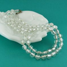 These unique glass beads are completely clear, and with their silver foiled inner core, the necklace looks like shimmering waterfall. Small silver tone beads complement and separate each shining bead, and form the ends of the two strands. Venetian glass beads are heavenly, with quality and shine like no other. These clear foiled vintage beads are a rarity.