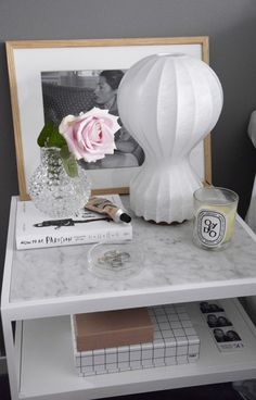 Achille Castiglioni's Gatto lamp for FLOS adds an elegant touch to a marble bedside table, matching the soft gray hues of ths interior.