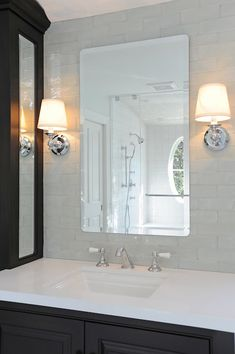 Bathroom with black-brown vanity and cabinets which pair with white Caesarstone counterops framing undermount sinks with hot and cold faucet.