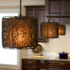 These funky woven cylindrical pendants lights are positioned over a kitchen island, adding a contemporary touch to this transitional kitchen.
