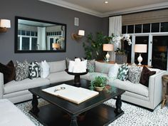Playful arm sconces, sophisticated fabrics, a custom rug and the balance of masculinity and femininity create a family room with broad appeal. The patterned throw pillows and rug add visual interest within an overall neutral color palette.