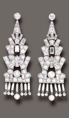 AN ELEGANT PAIR OF ART DECO DIAMOND EAR PENDANTS, BY CARTIER  Each set with a circular-cut diamond, suspending an articulated series of baguette, single and old European-cut diamond links, trimmed by a baguette, single and circular-cut diamond fringe, mounted in platinum, circa 1925 Signed Cartier London, no. 2950