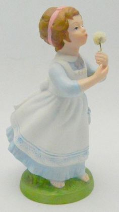 """SOLD - Vintage used hand painted matte or bisque porcelain figurine of a girl in a blue dress with a white pinafore blowing dandelion fluff or seeds.  This figurine was called """"Wishful Thoughts"""" and was made in 1982 exclusively for Avon. The figurine is marked on the bottom.  #Vintage #Avon #Collectible #Figurine"""