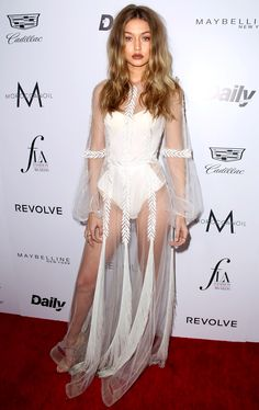 GIGI HADID in a sheer white Yanina Couture dress with sequin and fringe detailing, plus nude sandals and a brown lip, at The Daily Front Row Fashion Los Angeles Awards.