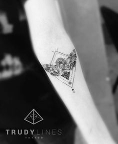 Graphic moth tattoo on the left inner forearm.