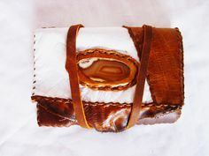 """Brown/white sliced agate with white&brown leather wallet.  """"The stone was given its name by Theophrastus, a Greek philosopher and naturalist, who discovered the stone along the shore line of the river while searching for algy Achates sometime between the 4th and 3rd centuries BC."""""""